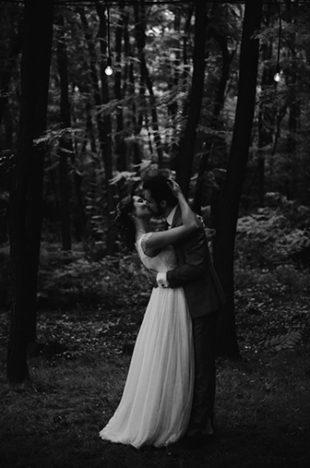 Un couple de mariés qui s'embrasse tendrement dans une forêt
