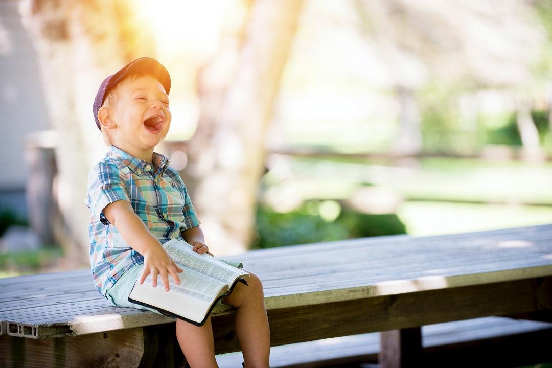 enfant assis sur un banc qui rit en lisant un livre