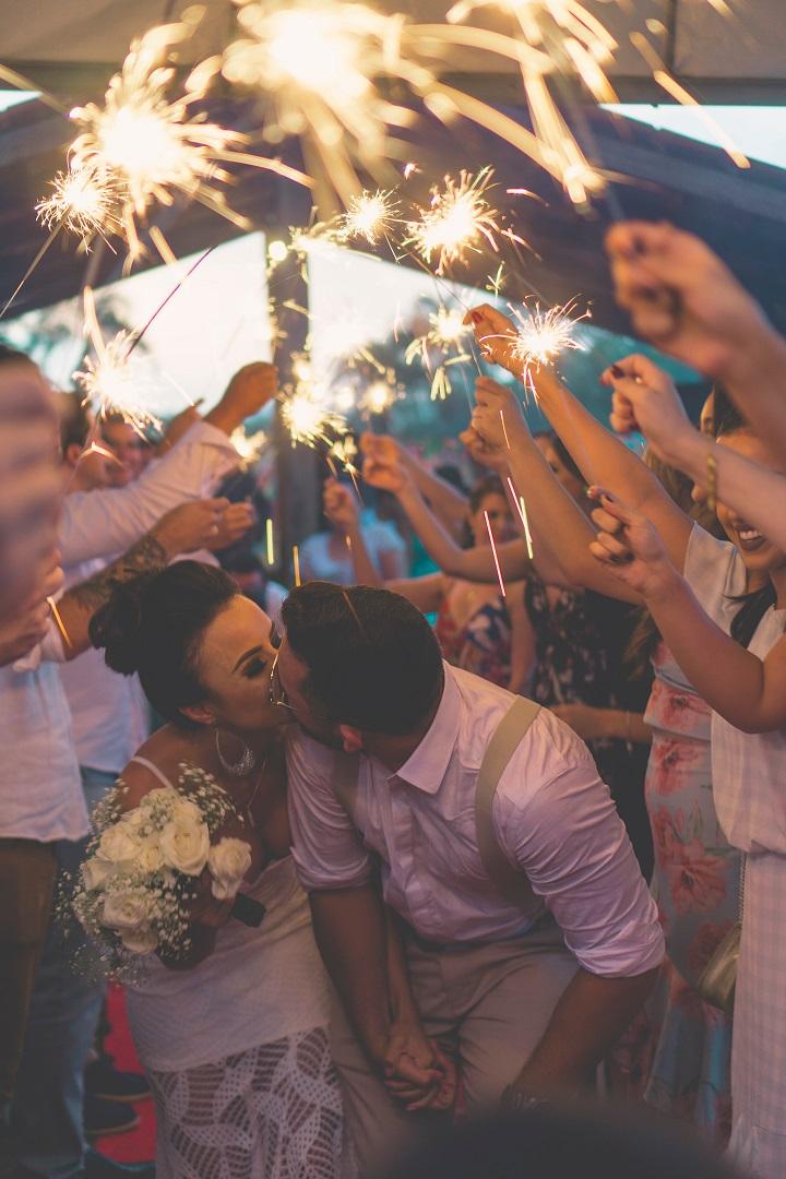 Couple de mariés qui s'embrassent devant leurs invités