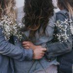 Groupe d'amies qui tiennent des fleurs dans leurs mains
