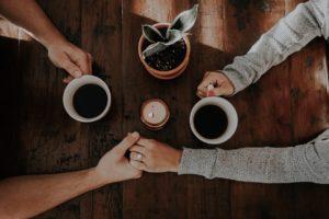 MAINS D'UN COUPLE QUI BOIT UN CAFE