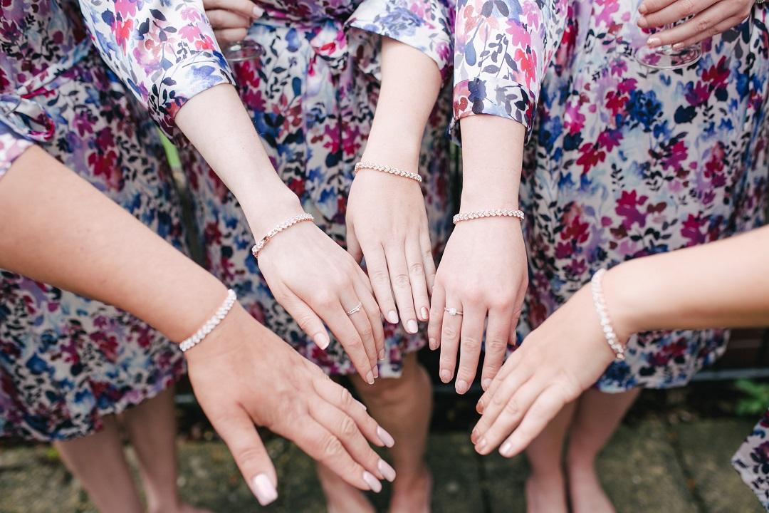 Quatre mains de demoiselles d'honneur qui portent le même bracelet
